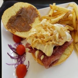 open-faced sandwich with sliced corned beef, swiss cheese, french fried onions, honey mustard and date spread with a side of french fries