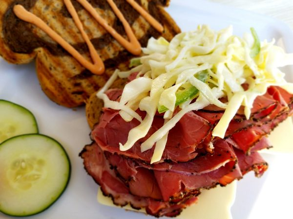 open-faced pastrami sandwich on sliced rye bread with swiss cheese, coleslaw and russian dressing
