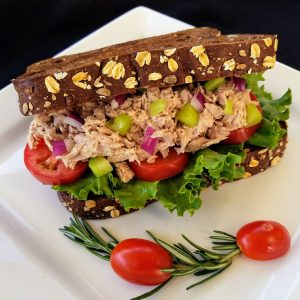 tuna sandwich on wheat bread with lettuce and tomatoes
