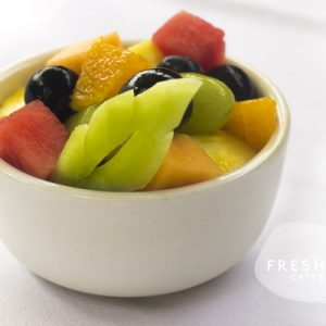 small bowl of cubed pineapple, honeydew, cantaloupe and grapes