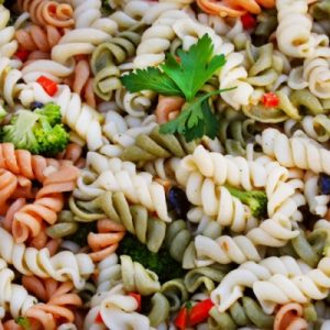 spiral pasta with veggies and parsley garnish