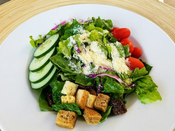 green salad with cucumber slices, tomatoes, croutons and parmesan cheese