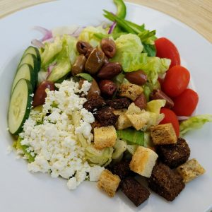 green salad with sliced cucumbers, tomato, purple onions, kalamata olives, bell peppers, feta cheese and croutons