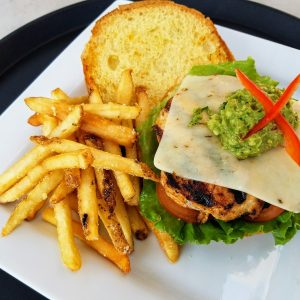open-faced grilled chicken sandwich with lettuce, tomato, pepperjack cheese, guacamole and a side of french fries