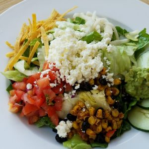 green salad with sliced cucumbers, diced tomato, corn and black bean relish, crumbled feta cheese and tortilla strips