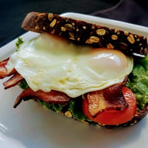 BLT sandwich on wheat with fried egg