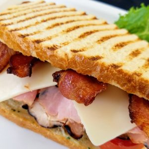 club panini with sliced turkey, ham, bacon, swiss cheese and tomato