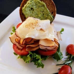 open-faced turkey sandwich on wheat bun with lettuce, tomato, swiss cheese and pesto sauce