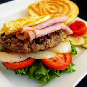 open-faced burger with lettuce, tomato, grilled onions, sliced ham and fried egg.